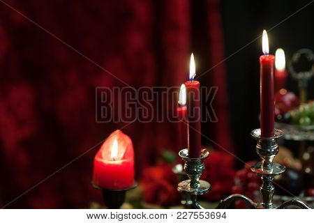 Red Candles On A Red Velvet Background. Fire Burns. The Dark Still Life