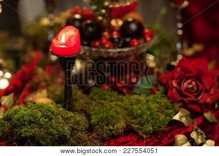 Dark Still Life In Red Tones With Candles, Moss And Roses. Horizontal Frame