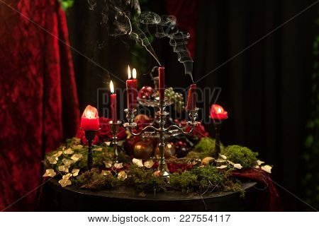 Dark Still Life In Red Tones With Candles, Moss And Roses. Smoke From Candles