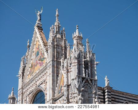 Exterior Of The Cathedral Of Siena Showing The Mosaics At The Top Of The West Facade And Scupltutes