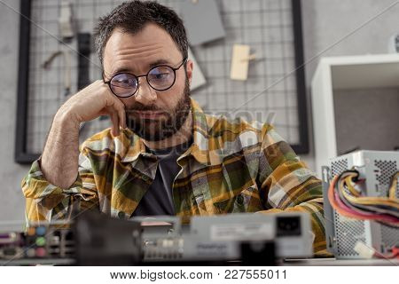 View Of Discouraged Repairman Looking At Broken Pc