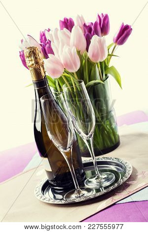 Two Empty Champagne Flutes And A Bottle Of Sparkling Wine