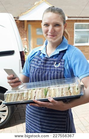 Portrait Of Female Caterer Delivering Tray Of Sandwiches To House Checking Text Message On Mobile Ph