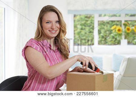 Portrait Of Woman Using Knife To Open Package At Home
