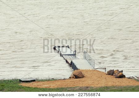 Wooden Pier On A Lake In The Afternoon In Windless Weather