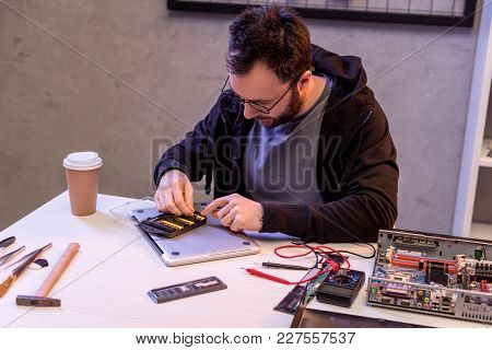 Man Choosing Attachments Before Fixing Digital Tablet