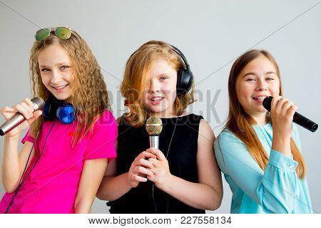 A Portrait Of Girls Singing In Headphones