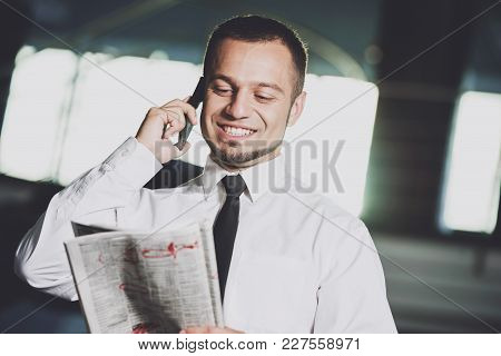 Unemployed, Smiling Man Is Looking For A Job In The Newspaper And Calling.