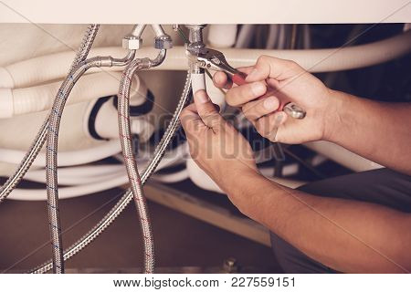 Hands Repairing The Plumbing Pipes Of An Electric Boiler With A Spanner. Close-up.