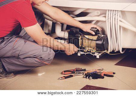 Male Plumber Fixing Sink Pipe In Bathroom.