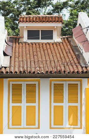 Bright Yellow Window Shutters Of Small House Closed By Sunny Day