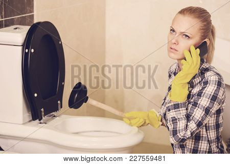 Plumber With Rubber Plunger In A Bathroom.