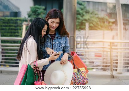Two Beautiful Cheerful Asian Young Woman With Mobile Smart Phone Holding Shopping Bags Together Walk