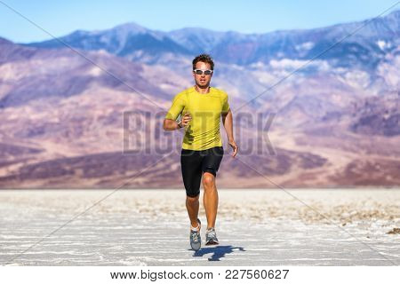 Running man - sprinting athlete runner in summer desert nature landscape background. Wearable tech smartwatch device sportswear.