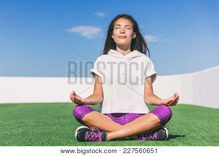 Yoga girl doing morning meditation. Wellness and health. Summer active lifestyle. Asian woman meditating outside on park grass.