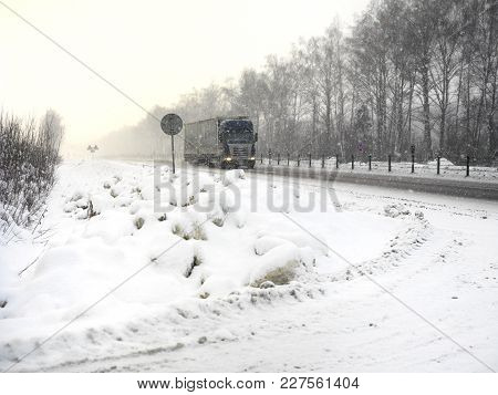 A Truck On The Motorway Under A Snowfall, Daytime Frosty Scene