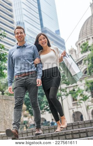 Woman and man shopping in Hong Kong Central. Interracial ouple walking outside with shopping bags. Urban mixed race Asian Chinese girl shopper and Caucasian man smiling happy living in city.
