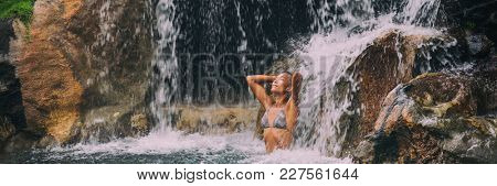 Waterfall woman relaxing in spa resort pool banner. Panoramic crop, wellness relaxation health concept in nature tropical travel vacation background. Beautiful Asian bikini girl. Landscape horizontal.