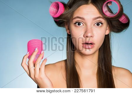 Surprised Young Girl Wants A Beautiful Hairstyle, On Her Head Big Pink Hair Curlers