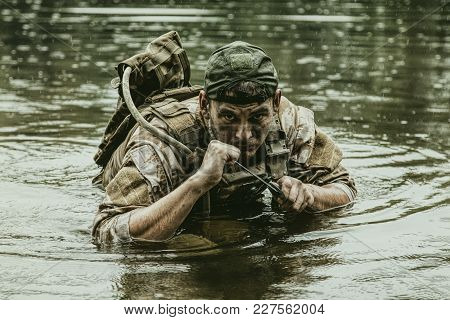 Private military contractor PMC in baseball cap during river raid in the jungle waist deep in the water and mud poster