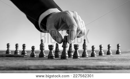 Greyscale Image Of A Male Hand Wearing Suit Reaching Dark Queen Chess Piece At Table.