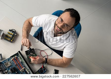 Overhead View Of Smiling Man Holding Multimeter And Magnifier In Hands