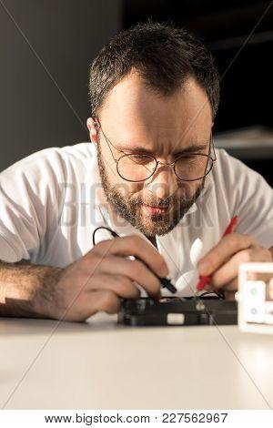 Man Using Multimeter While Testing Hard Disk Drive