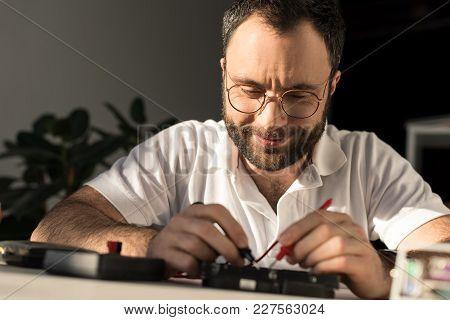 Smiling Man Using Multimeter While Fixing Pc