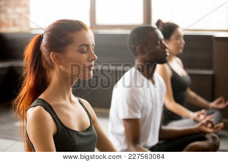 Group Of Young Sporty Afro American And Caucasian People Practicing Yoga Lesson, Sitting In Sukhasan