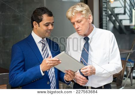Young And Senior Men In Ties Looking At Tablet Screen Attentively. Two Businessmen Reviewing Present