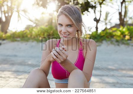 Sporty Pretty Female Works On Her Abs Outdoor At Beach, Wants To Be Healty And Fit, Has Running Work