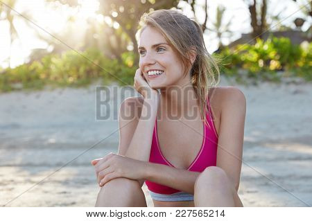 Attractive Female Jogger Or Athlete Has Workout At Beach, Rests Outside, Admires Sunshine, Looks Wit