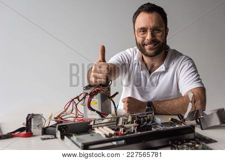 Man Showing Thumb Up While Smiling At Camera Against Broken Pc