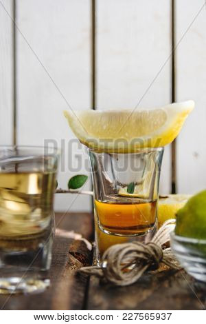 Shots Of Tequila, Lemon Lime And Salt On Wood Background