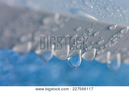 Drop of frozen water dripping from the blue transparency ceiling