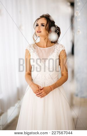 Beautiful Bride In White Wedding Dress Is Standing In Boudoir Room And Look Up. White Background