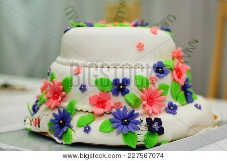 Wedding Cake In White Sweet Glaze With Colorful Flowers