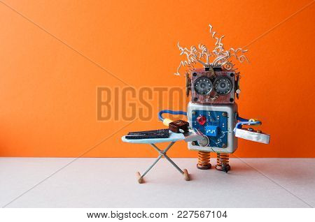Robot Home Assistant Ironing Black Pants With Steam Iron On The Board. Orange Wall Gray Floor Room I