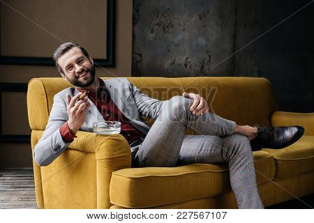 Handsome Laughing Man With Cigar And Ashtray Sitting On Sofa  In Loft Interior