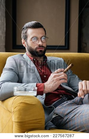Stylish Man With Cigar And Ashtray Sitting On Couch