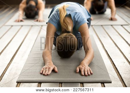 Yogi Woman And A Group Of Young Sporty People Practicing Yoga Lesson With Instructor, Stretching In