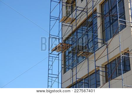 Scaffolding Round Building With Sky At Background.