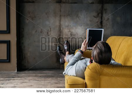 Back View Of Stylish Man Using Digital Tablet While Lying On Couch In Loft Interior