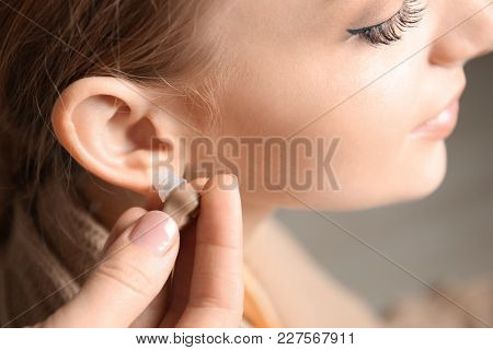 Doctor putting hearing aid in woman's ear, closeup