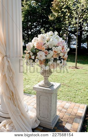 White Wedding Arch With Big Peach Bouquets On The White Stands