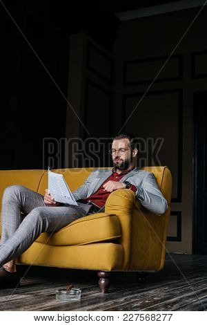 Handsome Man Reading Newspaper And Sitting On Couch, Ashtray With Cigar On Floor