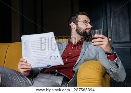 Stylish Man Holding Newspaper And Glass Of Cognac