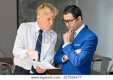 Executive And Manager Working On Document. Strict Boss Pointing At Paper And Scolding Employee For P