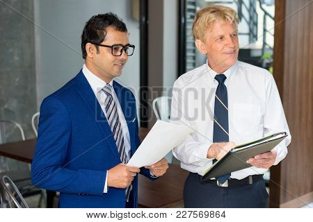 Senior And Junior Businessmen With Documents At Coworking Space. Two Positive Coworkers Coming Into