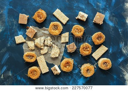 Middle Eastern Sweet Food On A Blue Background, Top View. Baklava, Halva, Sherbet, Sesame With Honey